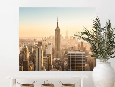 New York City. Manhattan downtown skyline with illuminated Empire State Building and skyscrapers at amazing golden sunset. USA.