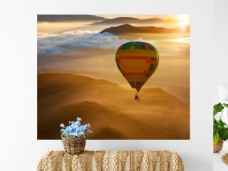 hot air balloon flying over misty mountains at sunrise - freedom and travel concept
