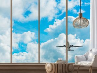 Commercial airline flying on blue sky and white fluffy clouds. Under view of airplane flying. Passenger plane after take off or going to landing flight. Vacation travel abroad. Air transportation.