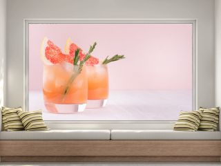 Summer cold cocktail with ice cubes, juice and slices grapefruit on pastel pink background.