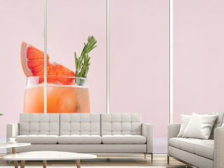 Cold grapefruit cocktail decorated twig rosemary and slice citrus on pink background.