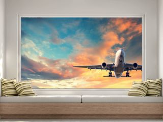 Landing airplane. Landscape with white passenger airplane is flying in the blue sky with multicolored clouds at sunset. Travel background. Passenger airliner. Business trip. Commercial aircraft