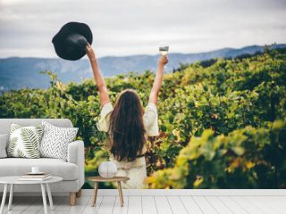 Woman relaxing in the vineyards. Woman holding glass with white wine.