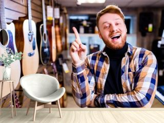 Irishman with red ginger hair and beatd is considering a guitars in a music store