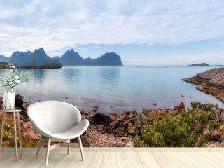 Beautiful rocky bay of the Norwegian fjord overlooking the distant mountains that are reflected in the surface of the sea under the blue sky.