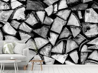 textured firewood background of chopped wood for kindling and heating the house. a woodpile with stacked firewood. the texture of the birch tree. toned in black white or gray color. banner