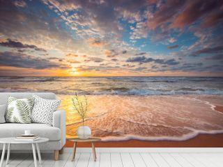 Beautiful cloudscape over the beach and sea at sunrise