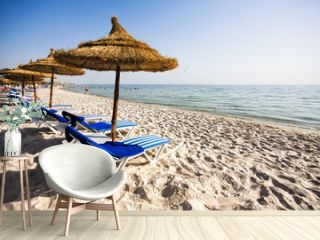 Nice beach with beach chairs and thatched umbrellas in Port El K