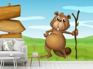 A beaver holding a wood beside a wooden signboard