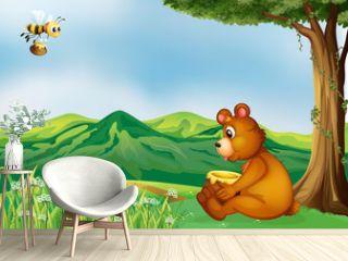 A bear sitting near a tree
