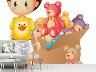 A boy beside a box of toys