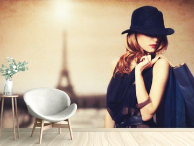 Redhead women with shopping bags on parisian background.