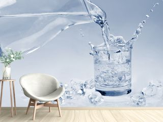 Ice cubes falling into a glass of water