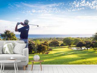 Man hitting golf ball down hill towards ocean and horizon
