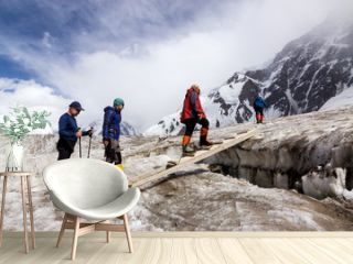 People Crossing Glacier Crevasse on Wood Shaky Footbridge Group of Mountain Climbers with High Altitude Boots and Clothing Crossing Ice Section During Ascent of Alpine Expedition in Asia Mountain Area