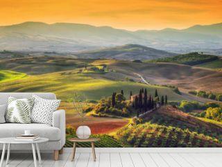 Tuscany landscape at sunrise. Tuscan farm house, vineyard, hills.