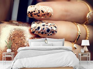 Golden holiday style bright manicure with gems and sparkles. Trendy accessories