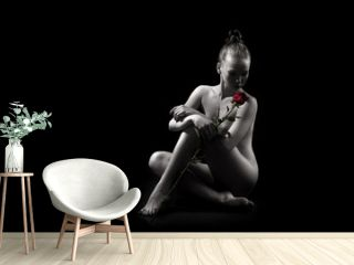 classic nude young sexy gir with red rose sits on floor on black background