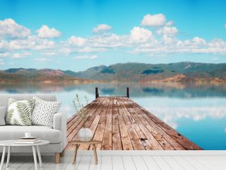 Perspective view of a wooden pier in a completely calm lake with reflections of the sky