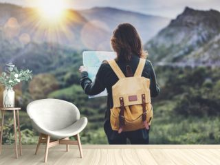 Hipster young girl with bright backpack enjoying sunset on peak of foggy mountain, looking a map. Tourist traveler on background valley landscape panoramic view mockup, flare. Vacation journey concept