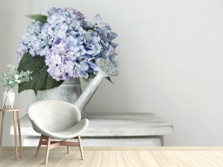 Hydrangea flowers in grunge zinc watering can on vintage wooden