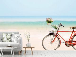 Old red Bicycle with basket flowers on blured beach tropical sea