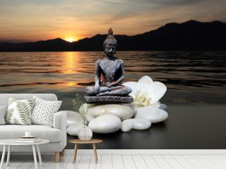 Zen or Feng-Shui background-Buddha,zen stone,white orchid flowers.In the background, the sun sets behind the mountains