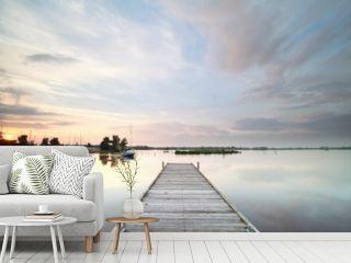 wooden pier on big lake at sunset