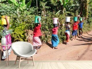 women carrying water from the village well to their homes in Tanzania in Africa