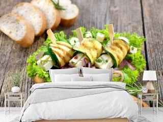 Zucchiniröllchen vom Grill mit Feta und Kräutern auf gerösteten Zwiebeln und Salat angerichtet - Greek appetizers: Grilled zucchini rolls with feta cheese on roasted onion rings and green salad
