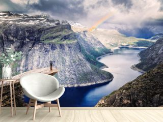 Male climber standing at the edge of cliff Trolltunga looking at rainbow against mountains, dramatic sky and amazing blue lake. Location: beautiful landscape of wild nature in Norway, Scandinavia.