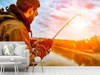 Young man fishing on a river from the boat at sunset