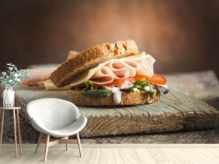 Tasty sandwich with ham, cheese, tomato and lettuce on wooden background