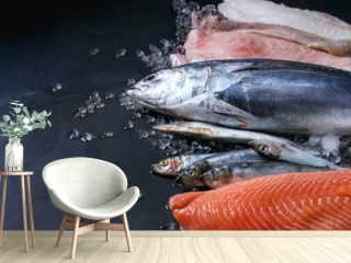 Variety of raw fresh fish. Whole tuna and herring, fillet of salmon, cod, red fish on crushed ice over dark wet metal background. Close up with space. Fish market concept