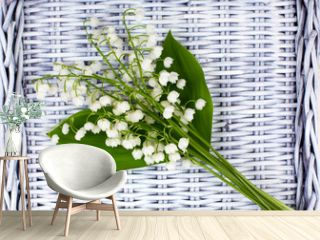 Fresh white lilies of the valley lie on a wicker tray.