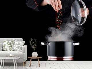 Modern chef in professional uniform adding spice to steaming pot