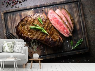 Grilled beef steak on wooden board. Top view.
