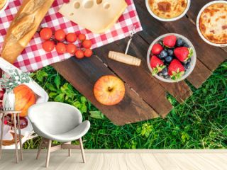 Picnic food on wooden board and green grass with copyspace