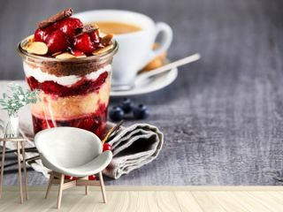 Layered fruit dessert in jar with cup of coffee