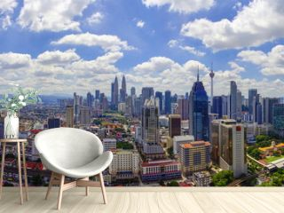 Panorama view of Kuala Lumpur city skyline with dramatic cloud formation and blue sky.