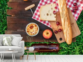 Picnic food and rose wine on green grass with copyspace
