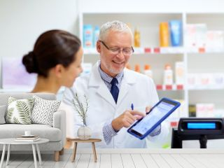 apothecary and customer with tablet pc at pharmacy