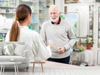Medicine, pharmaceutics, health care and people concept - Happy senior male customer paying for medications at a drugstore