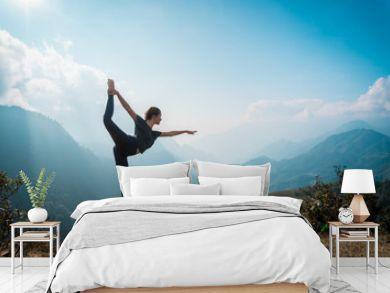 Woman training yoga, mountains on background