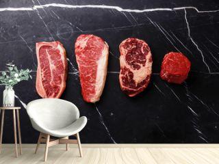 Variety of Raw Black Angus Prime meat steaks Blade on bone, Striploin, Rib eye, Tenderloin fillet mignon on dark marble background copy space