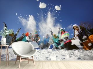 A group of friends of skiers and snowboarders fun throwing snow on top of the mountain.