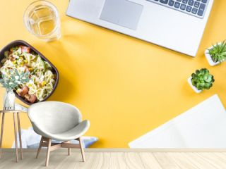 Vegetable salad with macaroni bowls with cheese in a container for lunch at the office workplace near the laptop. Top view, flat lay. Copyspace