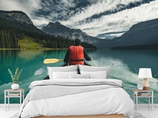 Young Man Canoeing on Emerald Lake in the rocky mountains canada with canoe and life vest with mountains in the background blue water.