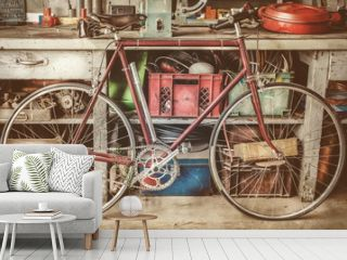 Vintage racing bycicle in front of an old work bench with tools