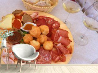 Leckeres toskanisches Vorspeisenbrett mit Schinken, Käse, Salami, Saucen und Coccoli sowie Brotkörbchen und Wein dazu